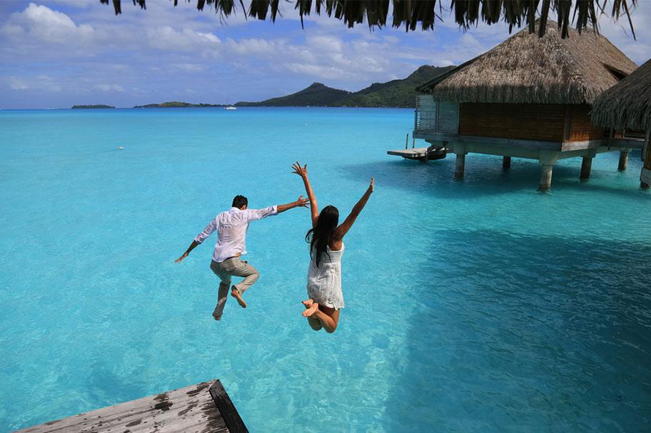 Paar springt von Bungalow in Wasser Honeymoon Polynesien